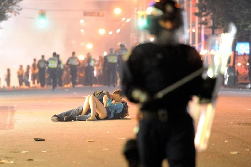 11. A couple kisses after the girl was knocked down by a policeman during the Vancouver riots, which occurred after Boston Bruins' win over the Vancouver Canucks, in June, 2011.