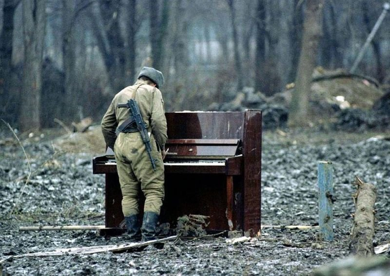 13. A Russian soldier plays an abandoned piano in Chechnya, 1994.