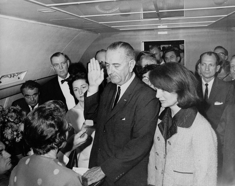 14. Jacqueline Kennedy in her suit stained with her husband's blood right after his assassination, as Lyndon Johnson takes the oath on 22nd November, 1963.