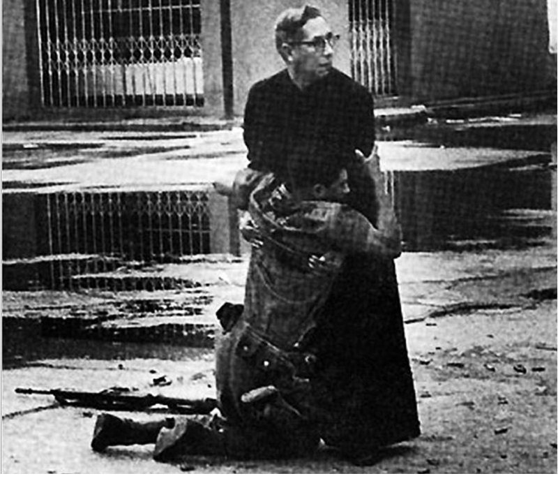 16. Navy chaplain Luis Padillo gives last rites to a soldier wounded by sniper fire during a revolt in Venezuela.