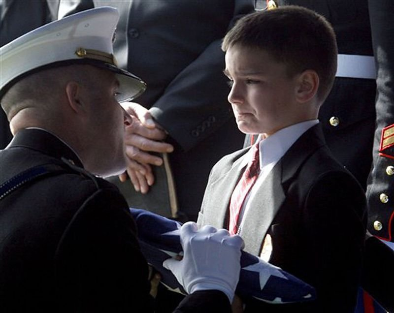 21. Marine Staff Sgt. Marc Golczynski's son accepts the flag for his father during a memorial service. He was shot a few weeks before he was due to return home.