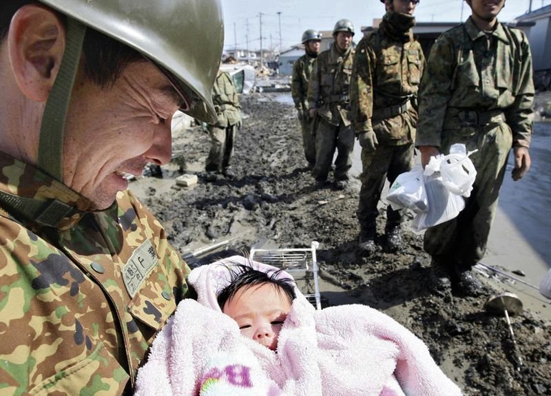 24. Soldiers rescue a 4-month-old baby girl who went missing for 4 days after the Japanese Tsunami in March, 2011.