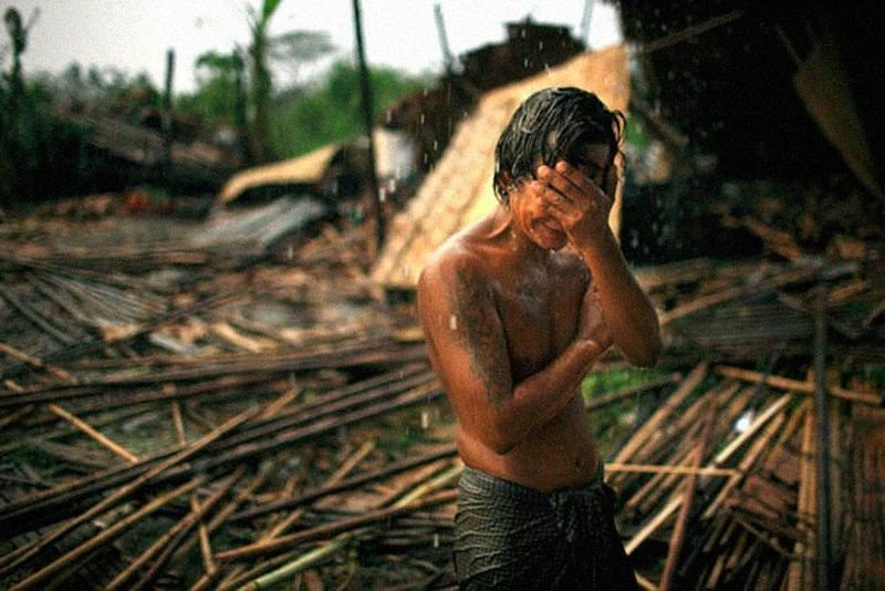 27. A young man holds his face in the rain in the city of Rangoon. Cyclone Nargis hit Myanmar leaving millions homeless and over 1,00,00 dead in May, 2008.