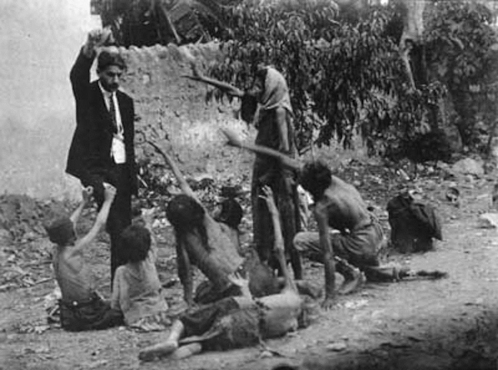 32. A Turkish official teases Armenian kids by showing them a piece of bread during the Armenian Genocide, 1915.