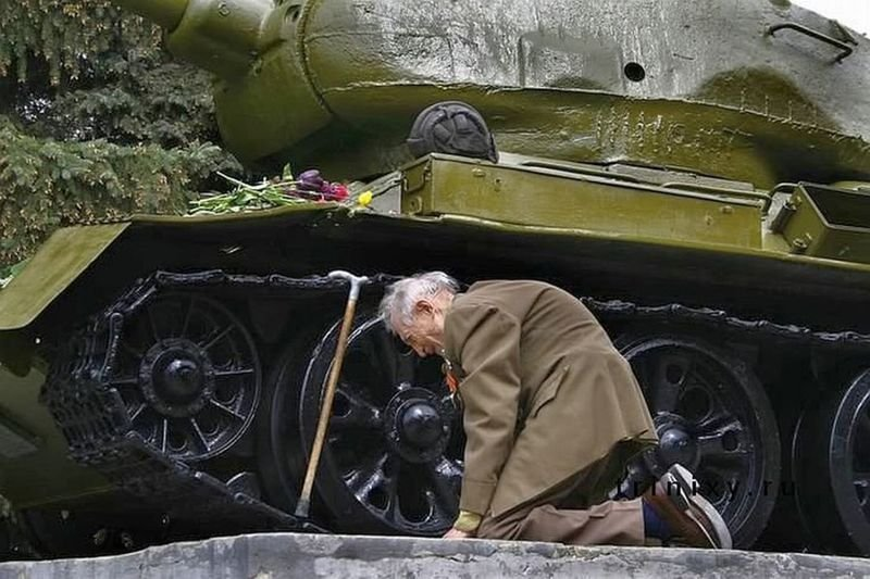 35. A war veteran from Russia kneels in front of a tank that he spent the war in. The tank is now a museum.