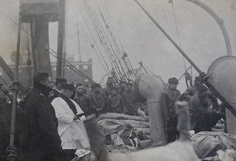 36. A priest prays over those who died in the Titanic accident before burying them at sea.