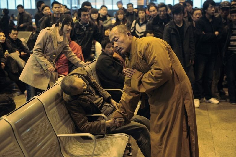37. A monk prays for an old man who died while waiting for a train in China.