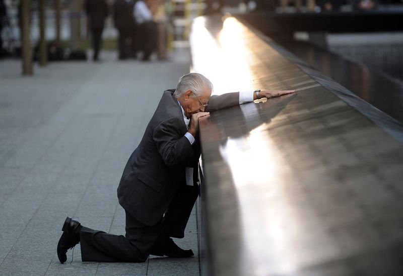 4. Robert Peraza falls to his knees as he touches his son's name at the 9/11 memorial.